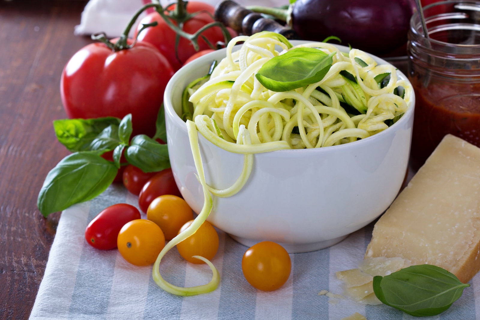 Zucchini noodles in a bowl with fresh vegetables and cheese ** Note: Shallow depth of field
