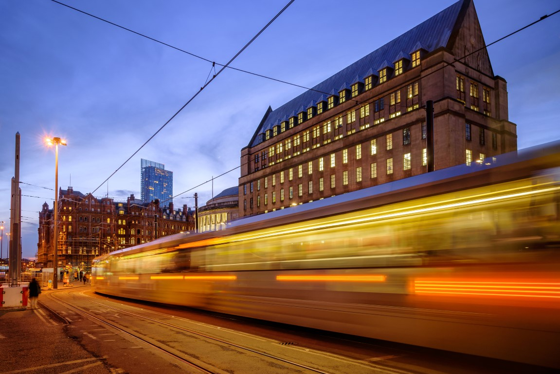 Metro tram passing in front of the new extension of the Manchester town hall Manchester England.